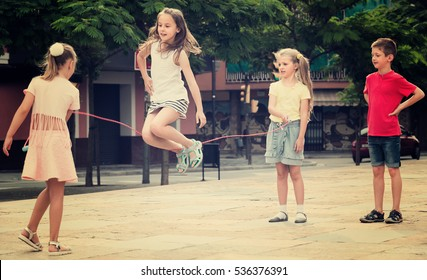 group of joyful children skipping together with jumping rope on urban playground