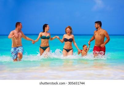 group of joyful friends having fun together on tropical beach