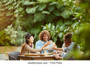 Group of joyful friends toasting with glasses of homemade drinks by served table in orangery