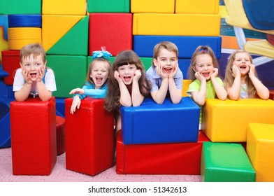 Group of joyful kids hiding behind large leather blocks