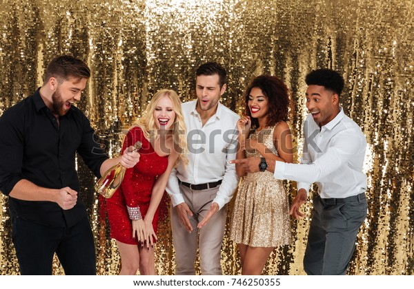 Group of joyful multicultural friends celebrating while standing with bottle of champagne isolated over shiny golden background