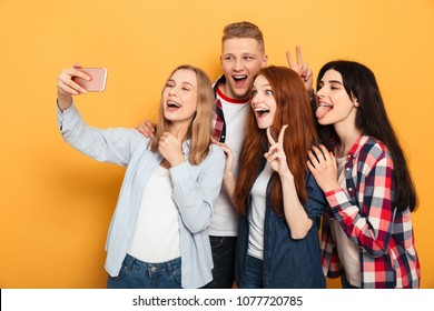 Group of joyful school friends taking a selfie while having fun together over yellow background