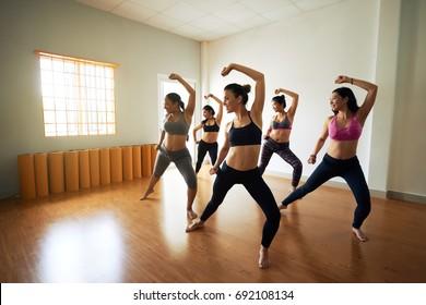 Group of joyful women wearing leggings and tops having fun while rehearsing dance in spacious studio