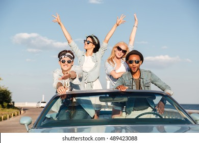 Group of joyful young people driving car in summer