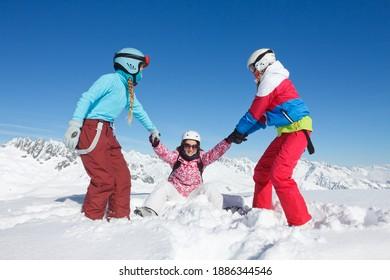 Groupe d'enfants et d'adolescents en vacances d'hiver en montagne jouant dans la neige sur des pistes de ski avec des équipements colorés