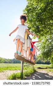 Group of kids balances on a beam for fitness and balance