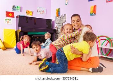 Group of kids boys and girls hug teacher