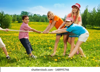 Group of kids, boys and girls playing pulling the rope in the dandelion field