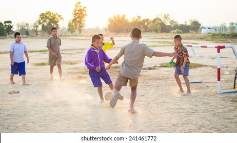 Group of the kids (boys) are playing soccer football for exercise in the sunshine day.