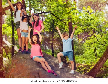Group of kids cheering standing on stone in forest