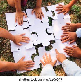Group kids/ children hands putting jigsaw/ puzzles pieces on grass.concept: cooperation, teamwork, learning, activity, business, working, helping, diverse, education, school, playing.Selective focus.