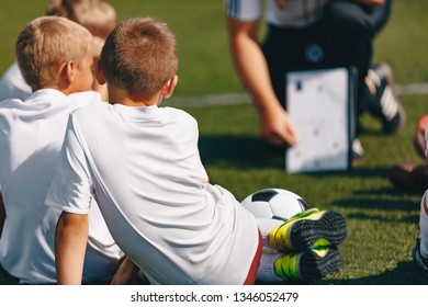 Group Of Kids Children In Soccer Team Having Training With Coach. Coach Explaining Tactics Using Board