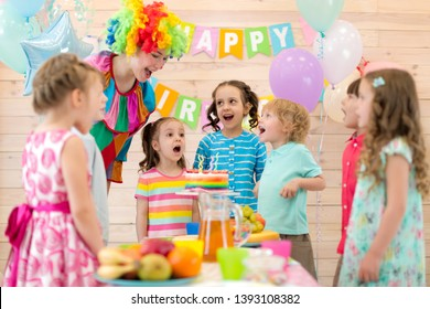 Group of kids with clown blowing candles on cake at birthday party