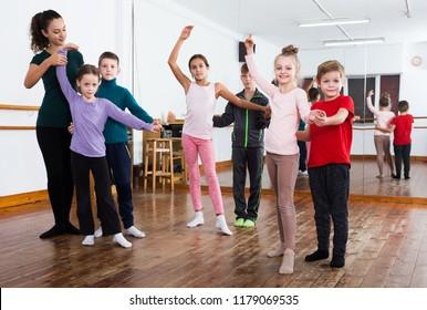 Group of kids dancing pair dance in dance hall