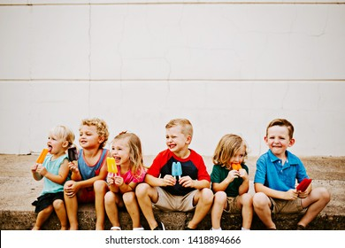 Group of Kids Eating Colorful Frozen Popsicles in the Summer