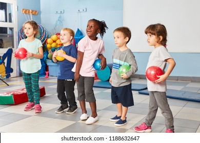 Group of kids in the gym in the international kindergarten with colorful balls