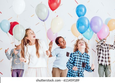 Group of kids having a party and dancing with balloons in their hands