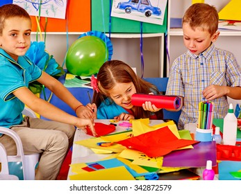 Group kids holding colored paper on table in kindergarten . Two male.