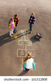 Group of kids jumping on the Hopscotch game drawn on the asphalt after school wearing autumn clothes