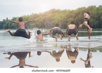 group of kids jumps into the river at summer vacations.