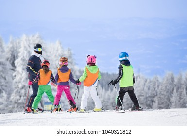 Group of kids learning how to ski on slope with instructor. Blue sky and white firs in background