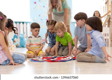 Group of kids learning time with clock toy in kindergarten