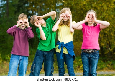 A group of kids making binoculars with their hands outside.