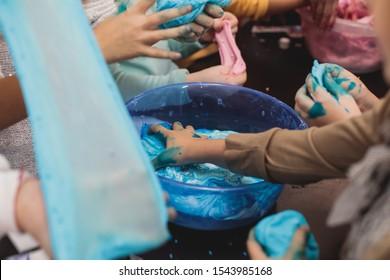 Gruppe von Kindern, die auf der KinderGeburtstagsfeier ein mehrfarbiges Schleim-, Rosa-, Blau- und weißes Schleimspielzeug machen, mit Schleim spielendes Kind, hausgemachte Schleime