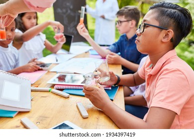 Group kids in multicultural summer school in chemistry tutoring class