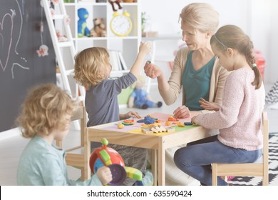 Group of kids on art classes with teacher in kindergarten