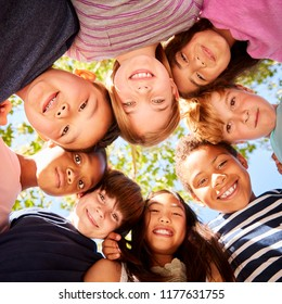 Group of kids outdoors looking down at camera, square format