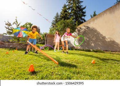 Group of kids play game throwing hula rings