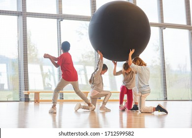 Group of kids play with an oversized ball in physical education