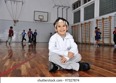 Group of kids playing basketball, young boy in front camera