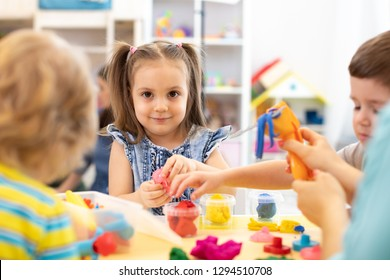 Group of kids playing with modeling clay in nursery