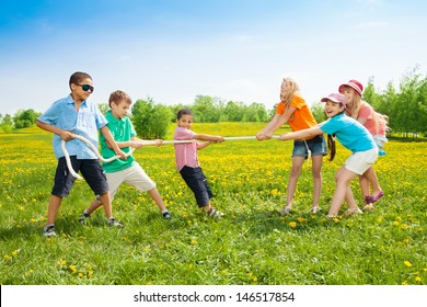 Group of kids playing pulling the rope in the dandelion field