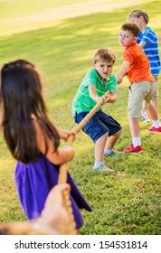 Group of Kids Playing Tug of War On Grass