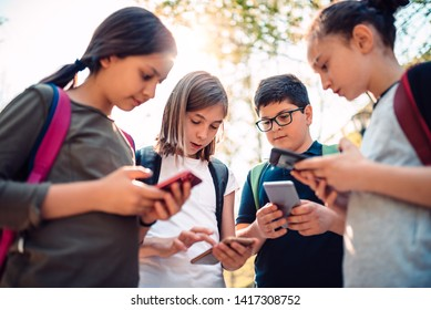 Group of kids playing video games on smart phone after school