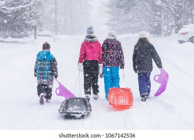 A group kids pulling toboggans/sleds down a snow covered winter neighborhood street during a snow storm/on a snow day.
