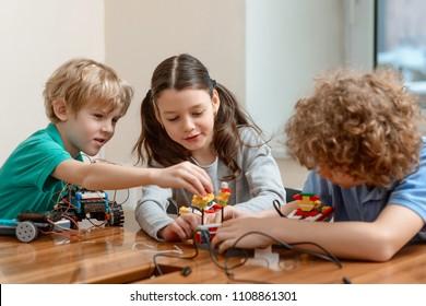 Grupo de niños haciendo un kit juntos. Chicos y chicas divertiéndose en el taller. Después de la actividad escolar