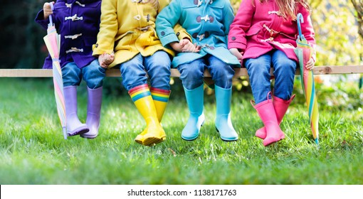 Group of kids in rain boots. Colorful footwear for children. Boys and girl in rainbow wellies and duffle coat. Rainbow foot wear and clothing for autumn or winter. Rainy weather outerwear and fashion.