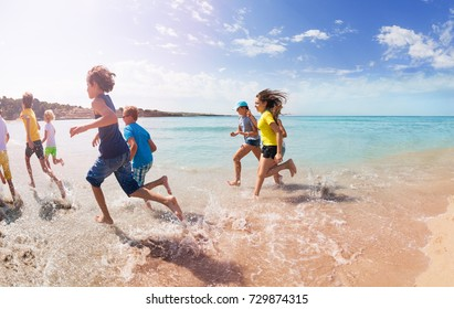 Group of kids run away on sandy beach