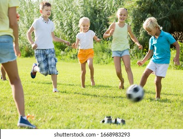 Group of kids in school age happily playing football together on green lawn in park