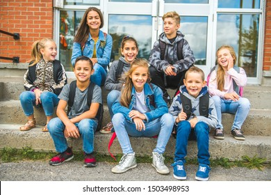 group of kids sit on the school stairs having fun