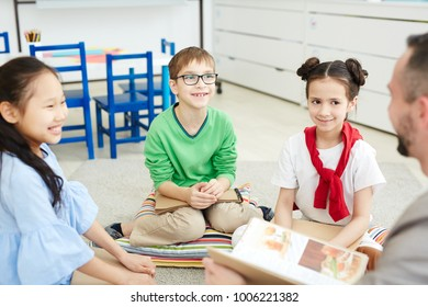 Group of kids sitting on pillows on the floor and listening to their teacher explanation