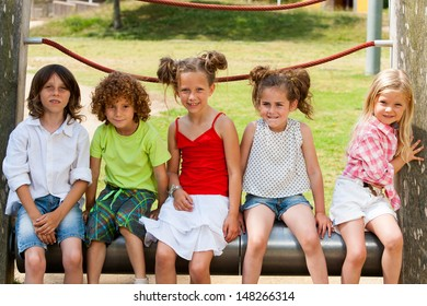 Group of kids sitting together in park.