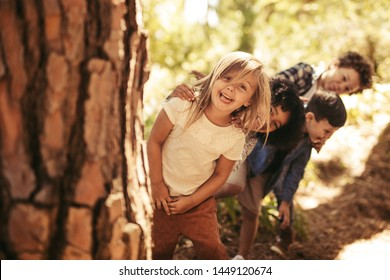 Group of kids standing in row and peeking behind a tree outdoors. Children playing hide and seek in a park.