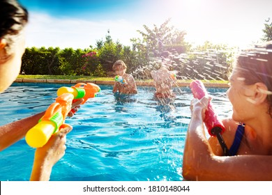 Group of kids in swimming pool shooting water-gun squirt pistol on sunny day