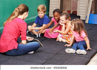 Group of kids talking about book with nursery teacher in preschool