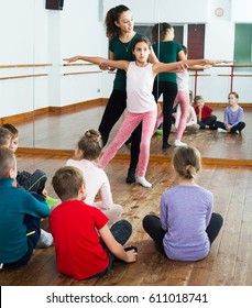 Group of kids with teacher dancing ballet in dance classGroup of kids with teacher dancing ballet in dance hall